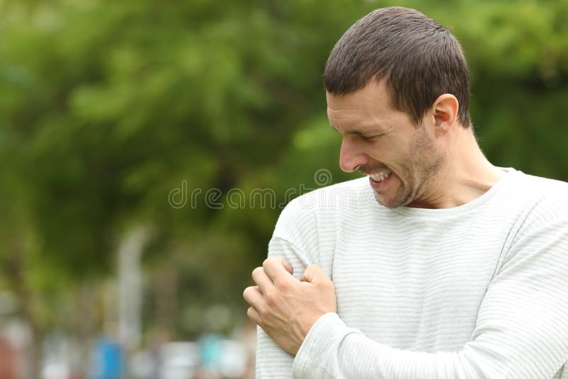 Man suffering itching cratching arm. Standing in a park stock photography