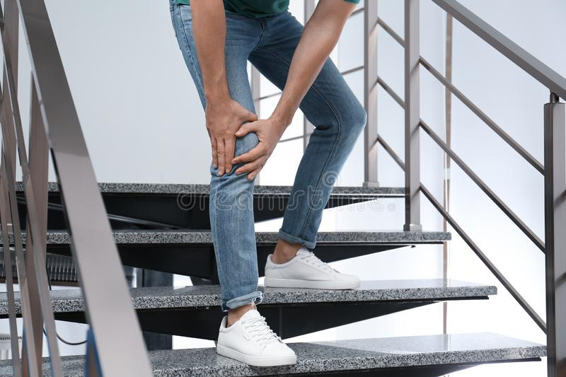 Man suffering from knee pain while going downstairs indoors. Health problems. Man suffering from knee pain while going downstairs indoors, closeup. Health stock images