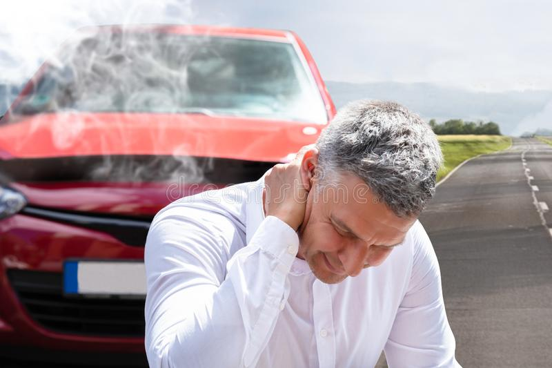 Man Suffering From Neck Pain In Front Of Breakdown Car. Close-up Of A Mature Man Suffering From Neck Pain In Front Of Breakdown Car royalty free stock photography