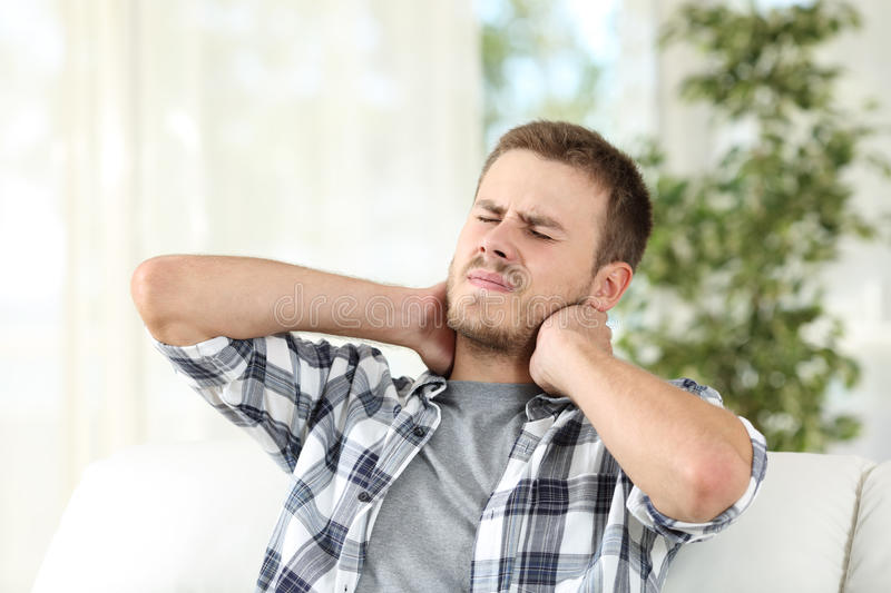 Man suffering neck pain at home royalty free stock photography