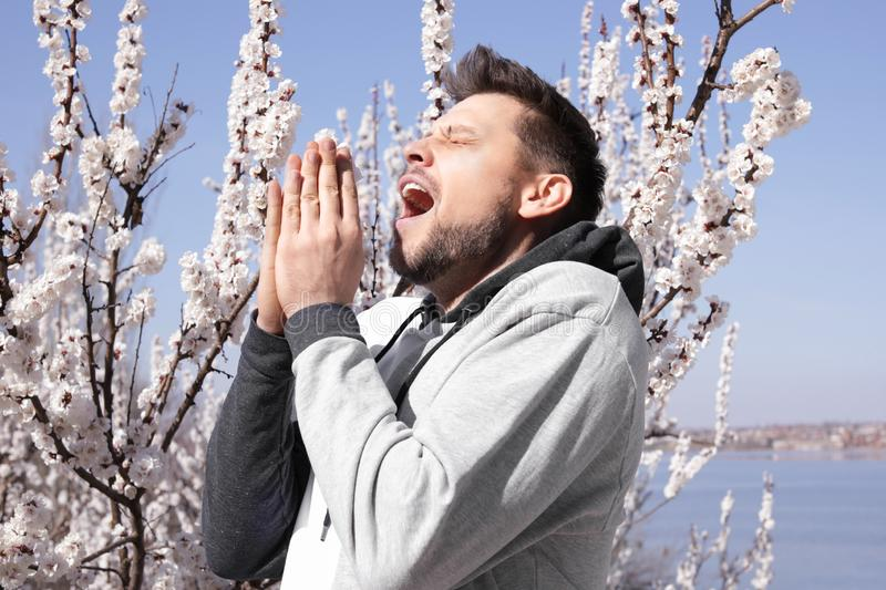 Man suffering from seasonal allergy outdoors. On sunny day stock photo