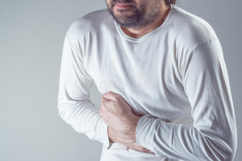Man suffering from severe abdominal pain, hands on stomach stock image