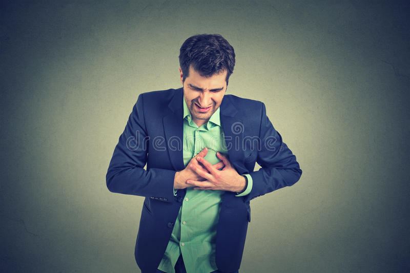 Man suffering from severe sharp heartache, chest pain. Heart disease royalty free stock image