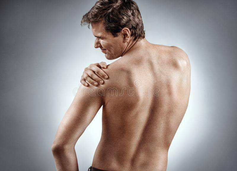 Man suffering from a shoulder injury. stock photos