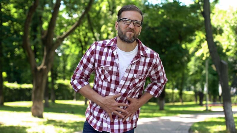 Man suffering stomach pain, gastritis symptom, digestion disease, healthcare stock image