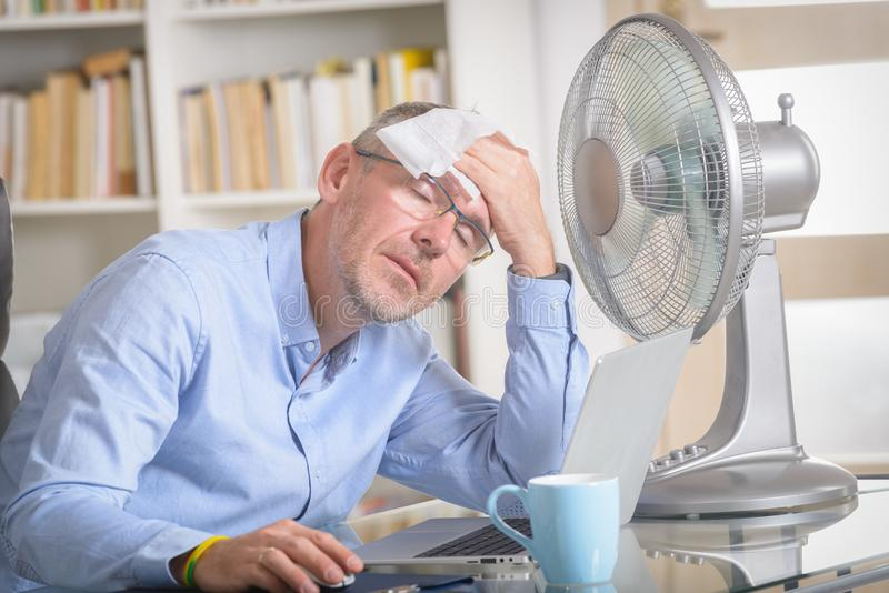Man suffers from heat in the office or at home royalty free stock photo