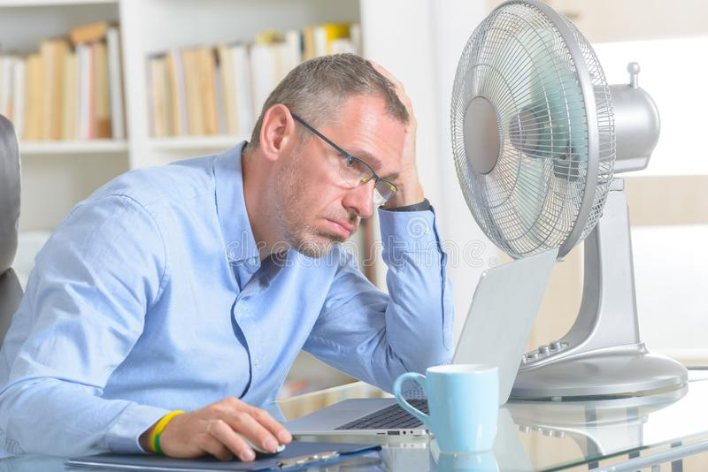 Man suffers from heat in the office or at home royalty free stock photography