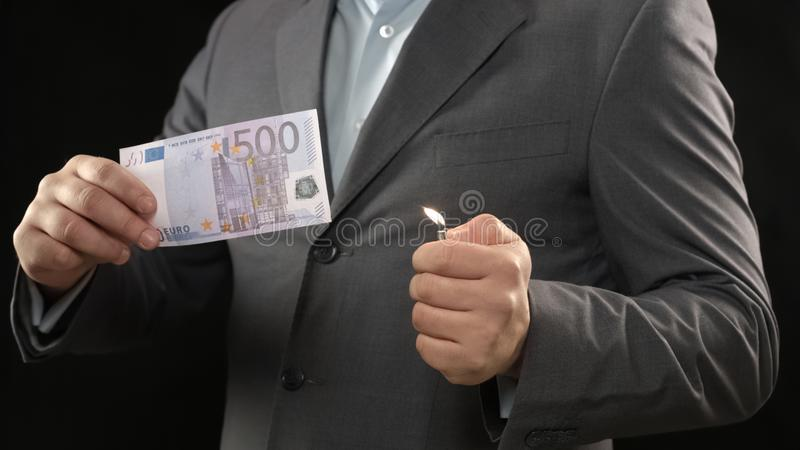 Man in suit burning five hundred euro bill, money wasting, bankruptcy concept. Stock photo royalty free stock images