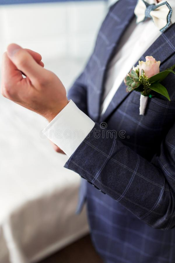 Man in a suit fastens shirt sleeve stock photo