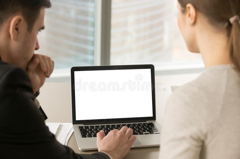 Two business people looking at mock up blank laptop screen. stock image