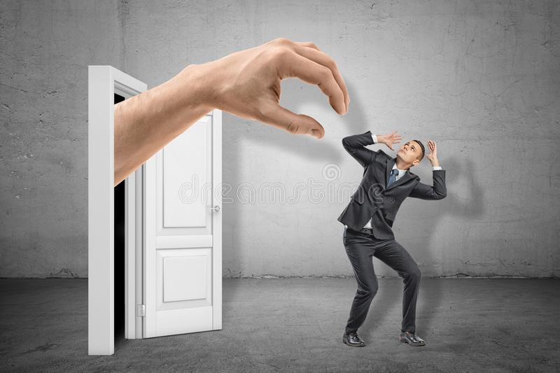 Man in suit covering head with hands to protect himself from huge hand emerging out of doorway. stock illustration