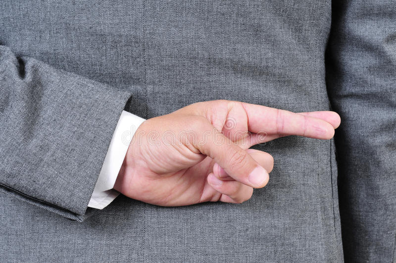Man in suit crossing his fingers in his back royalty free stock photo