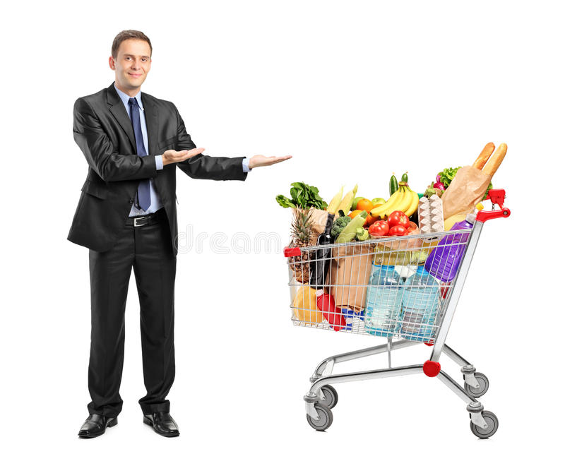Man in suit gesturing and shopping cart. Full length portrait of a man in suit gesturing and shopping cart on white background royalty free stock image