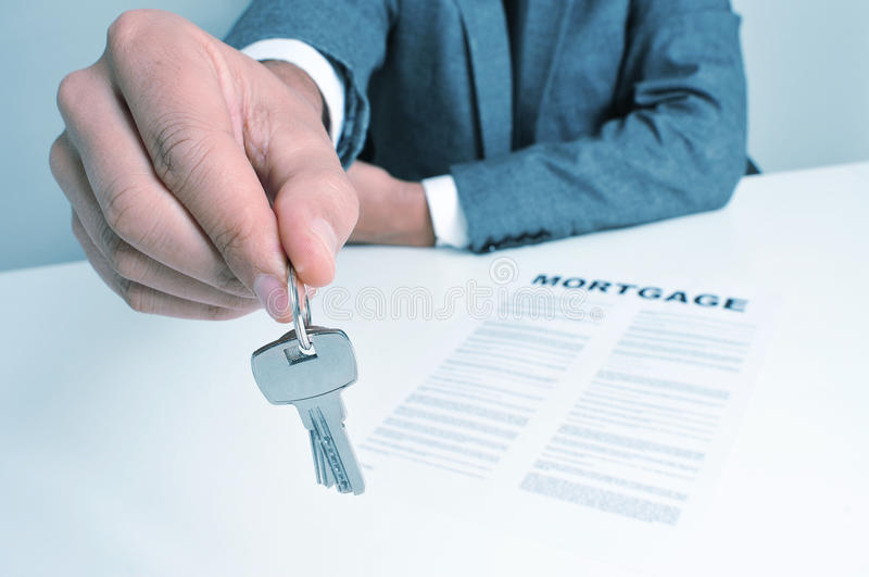 Man in suit giving the keys stock images
