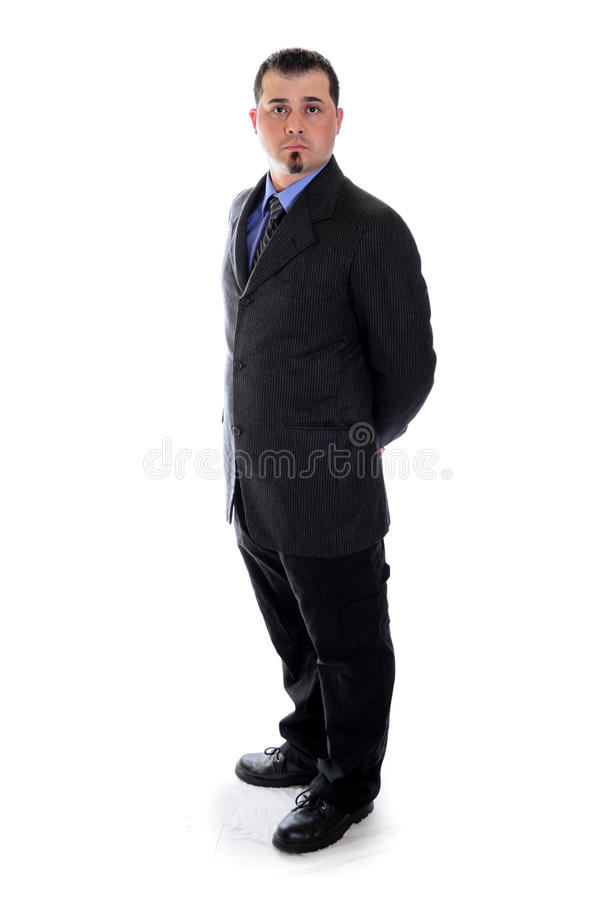 Man in suit holding his hands behind back. A man in a dark grey suit holding his hands behind his back stock photography