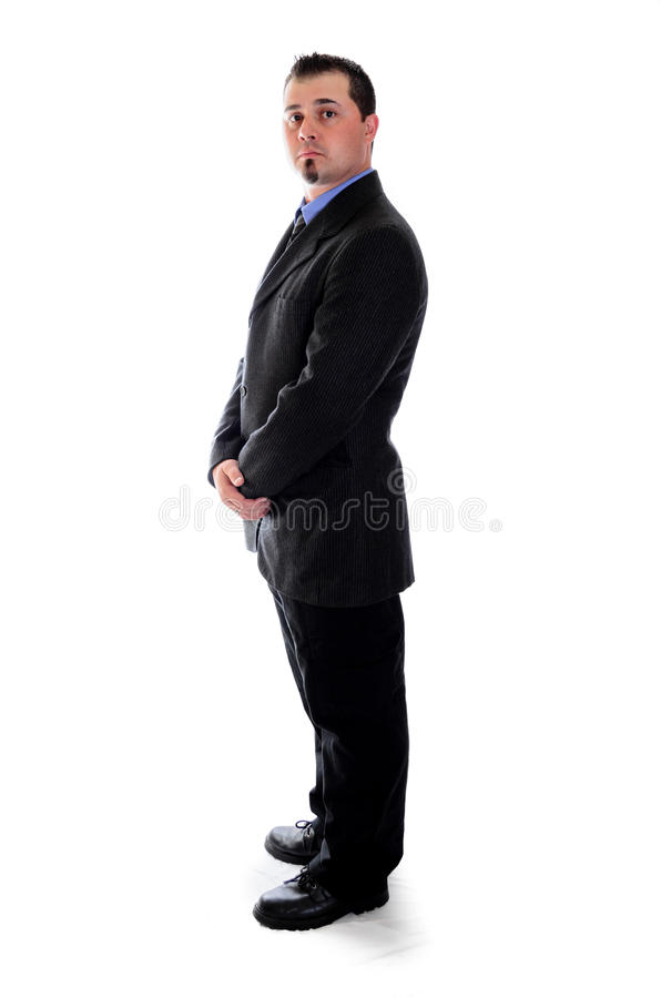 Man in suit holding his hands looking right. A man in a dark grey suit holding his hands stock photos