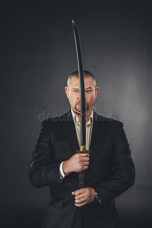 man in suit holding katana sword in front of his face royalty free stock photos