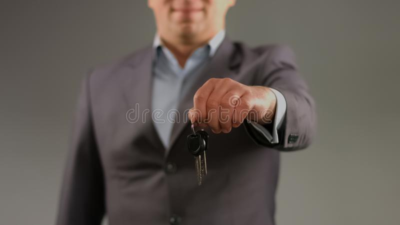 Man in suit holding keys, renting car or apartment, real estate agent profession. Stock photo stock photos