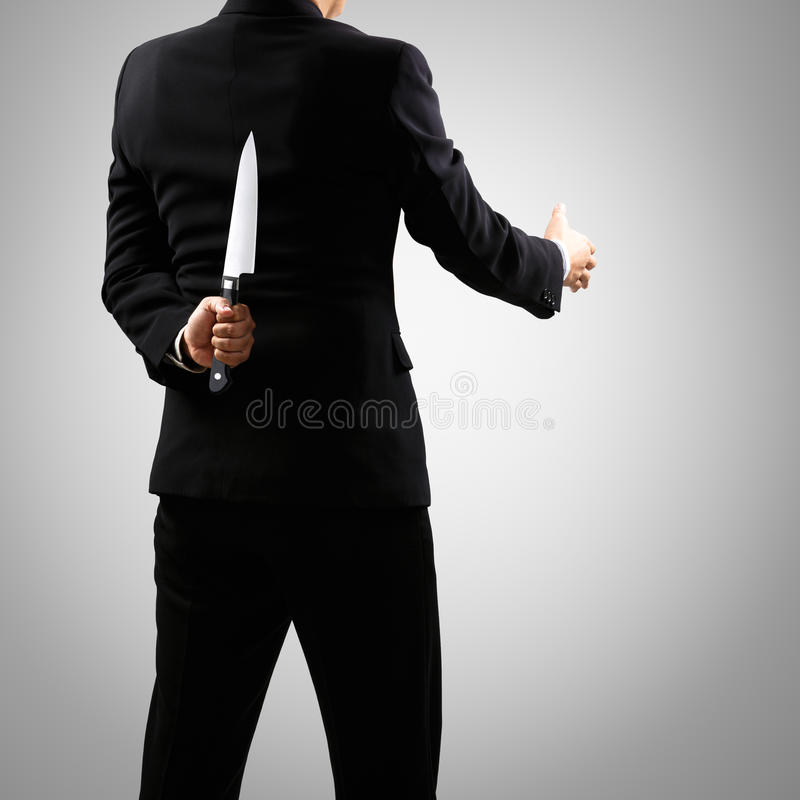 A man in suit holding knife behind back. Isolated on grey background stock photo