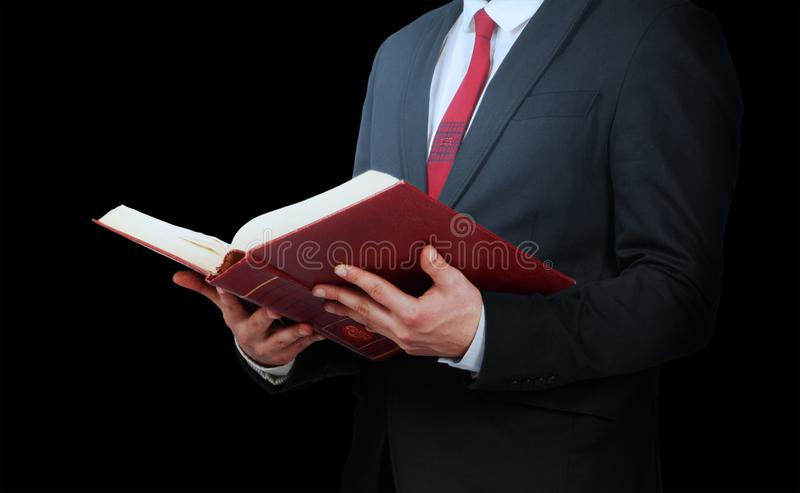 Man in suit holding opened book on a black background royalty free stock photos