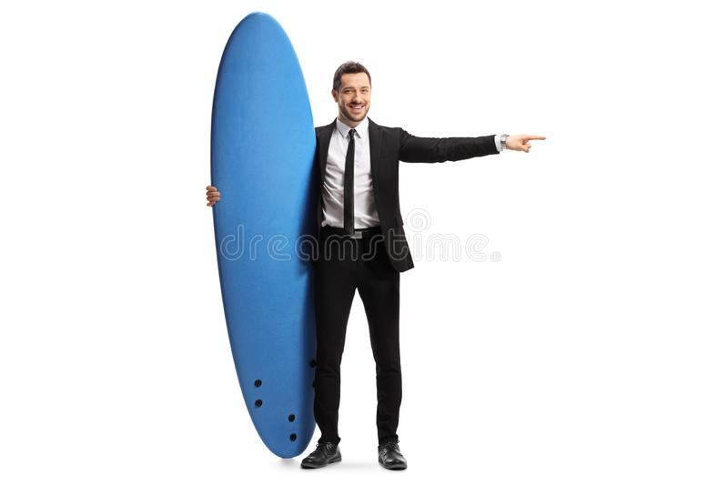 Man in a suit holding a surfing board and pointing to the side. Full length portrait of a man in a suit holding a surfing board and pointing to the side isolated stock photography