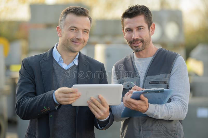 Man with suit holding tablet workman holding clipboard. Man royalty free stock photography
