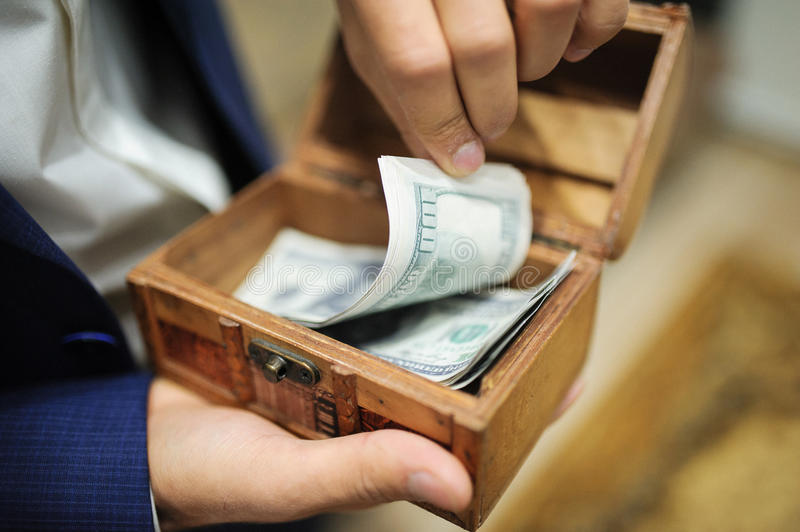 Man in suit holding tray full of money stock image
