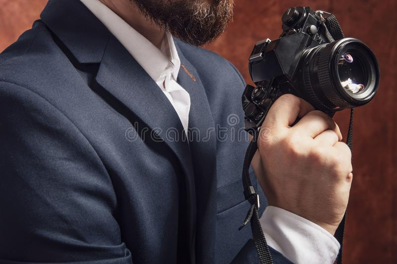 Man in suit holds old camera stock photo