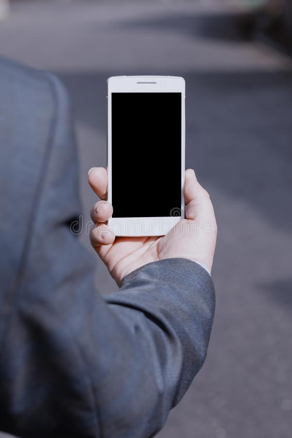A man in a suit holds a white smartphone. With the black screen in his hand stock images