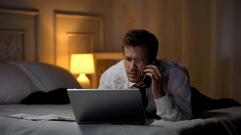 Man in suit lying on bed working on laptop and talking on phone, busy lifestyle stock photo