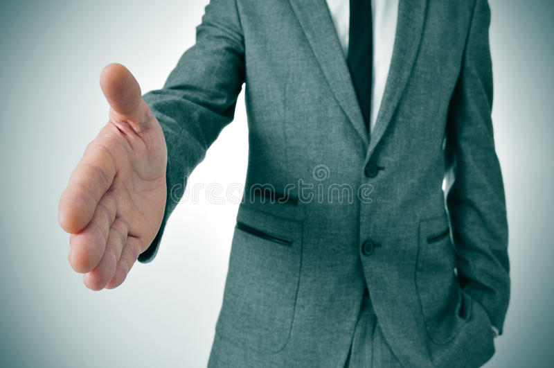 Man in suit offering to shake hands. Man wearing a suit offering to shake hands royalty free stock photo