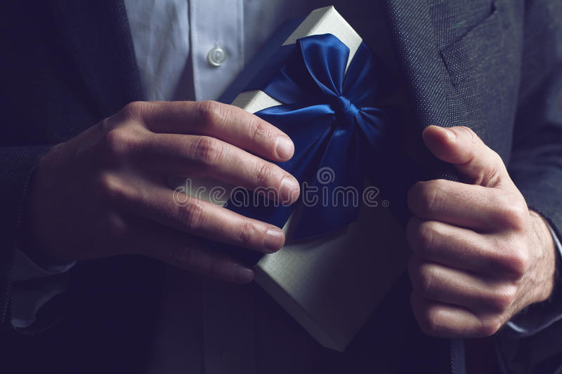 Man in suit opening a gift with blue ribbon. Horizontal close up of Caucasian man in black suit and white shirt taking out a large gift box with blue ribbon from stock photos