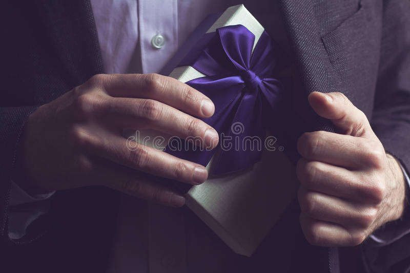 Man in suit opening a gift with purple ribbon. Horizontal close up of Caucasian man in black suit and white shirt taking out a large gift box with purple ribbon stock image