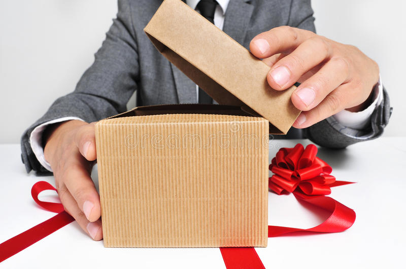 Man in suit opening a gift royalty free stock photography