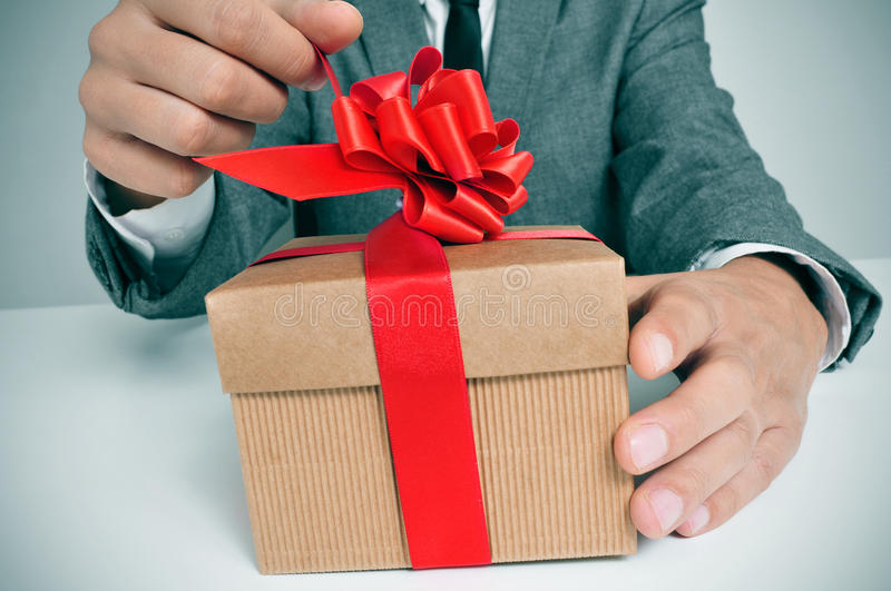 Man in suit opening a gift. Man wearing a suit sitting in a table opening a gift with a red ribbon royalty free stock photography