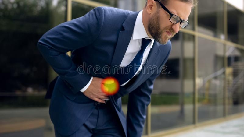 Man in suit overwhelmed with pain in stomach, chronic gastritis spot indicator stock images