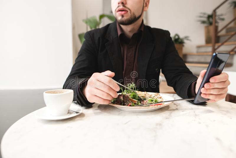 Man in a suit, a plate of salad, a cup of coffee in a cozy restaurant stock images