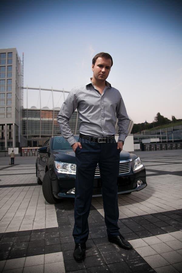 Man in suit posing near car. Handsome man in suit posing near car stock photos