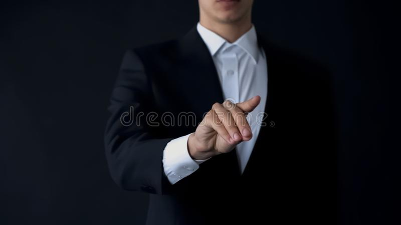 Man in suit scrolling virtual menu, choosing option, search for data, innovation stock image