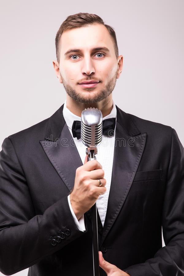 Man in suit singing with the microphone and smile. Isolated on white background. Showman concept royalty free stock photo