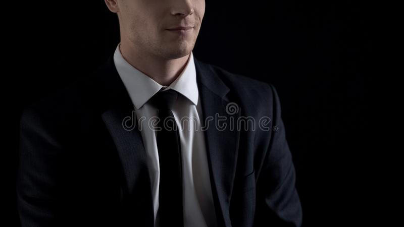 Man in suit smirking,  on black background, unfair business concept. Stock photo stock images