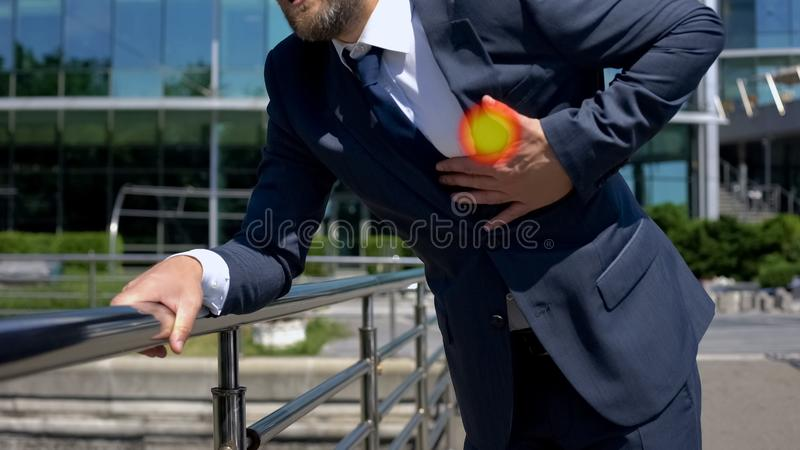 Man in suit suddenly feeling pain in chest, having heart attack outside office stock photos