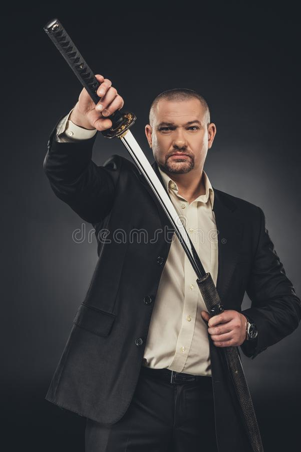 man in suit taking of his katana sword stock image