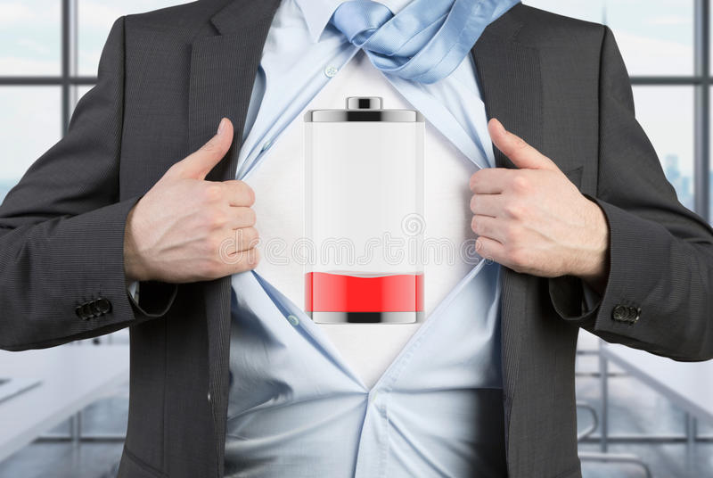 A man in a suit is tearing the blue shirt. Low level of power on the chest. Modern panoramic office background royalty free stock photography