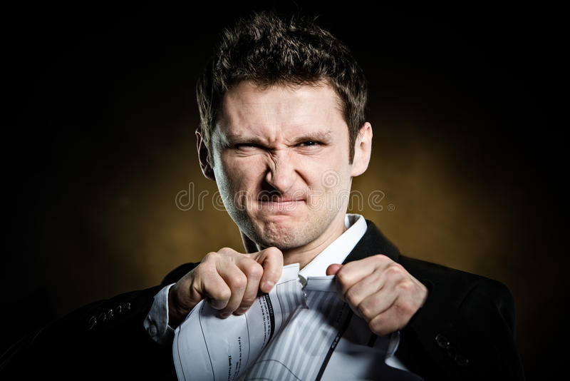 Man in a suit tearing furiously invoice. Or bill stock images