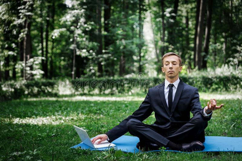 Man in a suit with tie. Business man relaxing in a park in the lotus position, he can`t relax in any way. Typing text on a computer with one hand. one eye mows stock photo