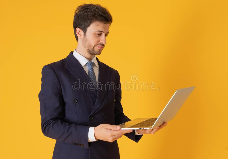 A man in a suit with a tie Handsome looking face with beard In the business man look Holding a notebook Looking at the notebook To royalty free stock images