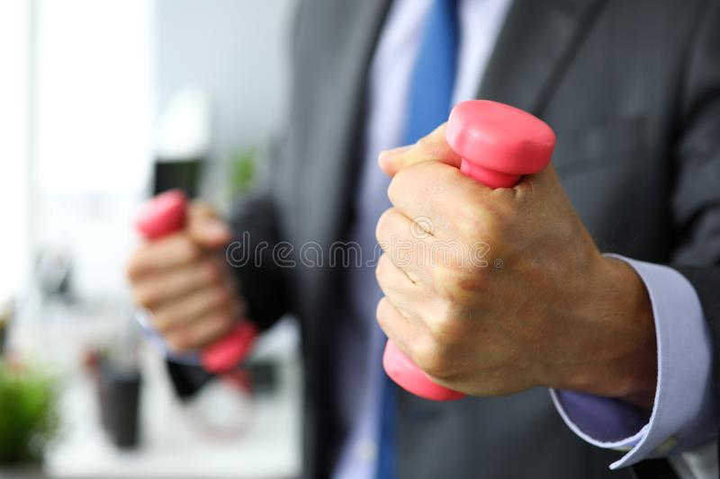 Man in suit and tie holding and pumping pink barbells stock photography