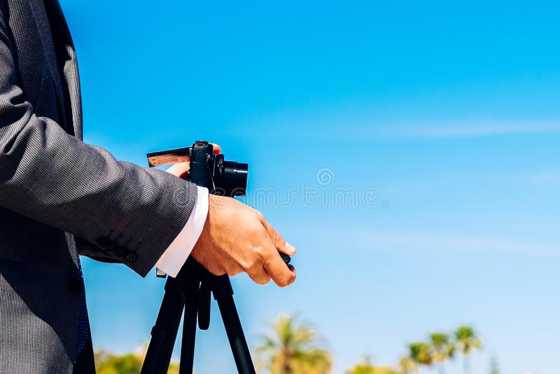 Man in a suit using a compact photo camera on a tripod to take a self-portrait to use as a profile in his business and social. Networks royalty free stock photo
