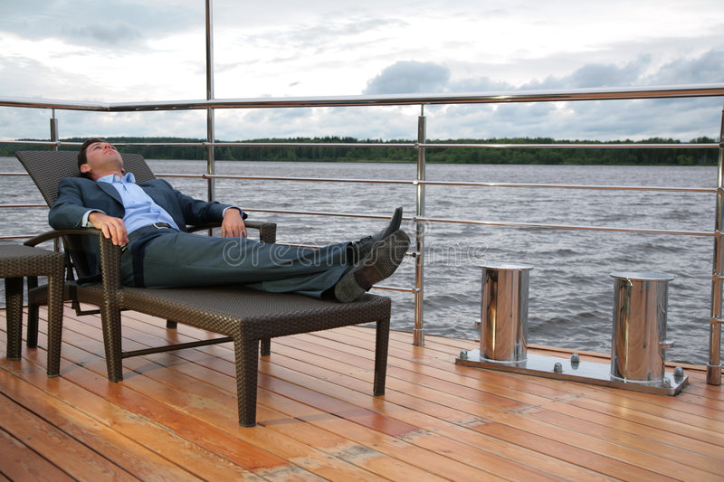 Download Man In Suit, Who Rests In Chaise Lounge On  Wharf Stock Photo - Image: 6582846
